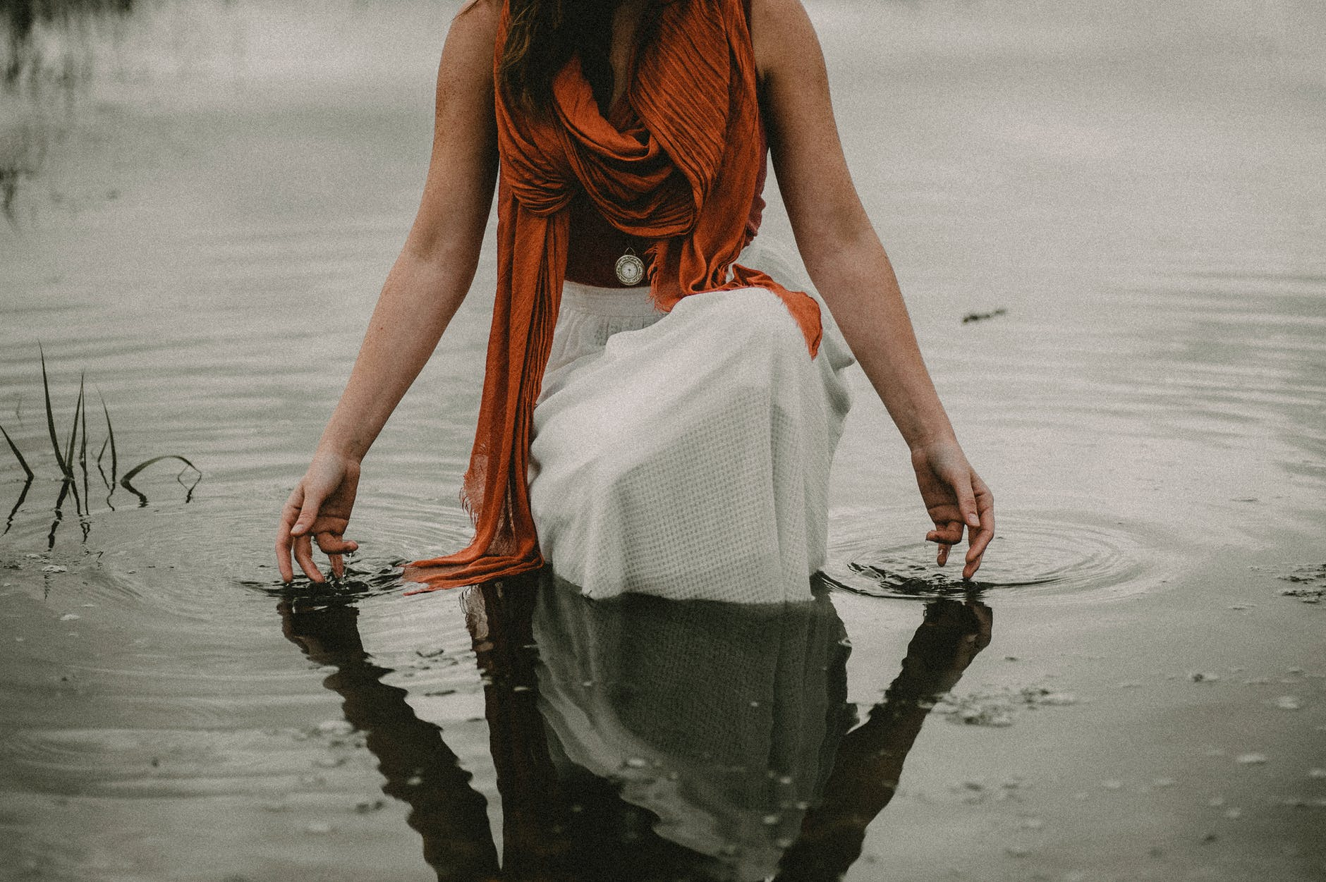 faceless tranquil woman touching water in lake