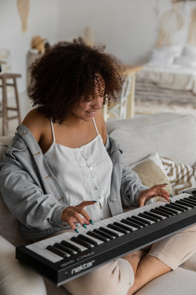happy ethnic woman playing synthesizer sitting on couch at home